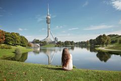 Woman resting in Olympiapark, Munich. Brunette sitting on the gr. Een grass by lake looking on green park with tv tower, Bavaria, Germany Royalty Free Stock Photos