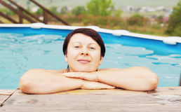 Woman is resting in an outdoor pool Stock Photo