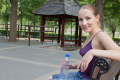 Woman resting in park after exercise. Sport fitness concept Stock Photos