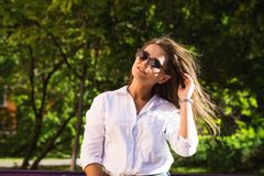 Woman resting at the park. girl in sunglasses, outdoor summer portrait Stock Photography