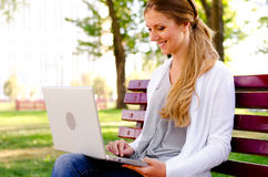 Woman resting in park and using laptop. Smiley young woman resting in park and using laptop Royalty Free Stock Photo