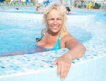 Woman resting in a pool. Portrait of an attractive middle-aged woman resting in a pool of blue water in the water park Royalty Free Stock Photo