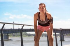 Woman resting after rn or jogging by the river in city on sunny. Day Royalty Free Stock Photography
