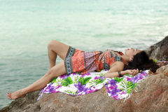 Woman resting on rocky beach Royalty Free Stock Photos