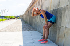 Woman resting after run by the wall. Stock Photography