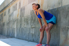 Woman resting after run by the wall. Stock Photo