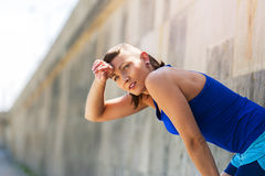 Woman resting after run by the wall. Royalty Free Stock Photos