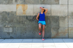 Woman resting after run by the wall. Royalty Free Stock Images
