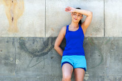Woman resting after run by the wall. Royalty Free Stock Photography