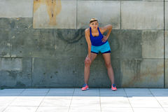 Woman resting after run by the wall. Royalty Free Stock Image
