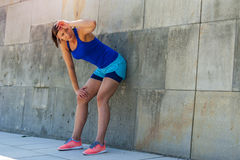 Woman resting after run by the wall. Stock Images