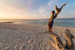 Woman resting on skeletal tree and watching a romantic colorful sunset on the beach of Tanjun Karang, Central Sulawesi, Indonesia. Wide angle shot, long Royalty Free Stock Photos