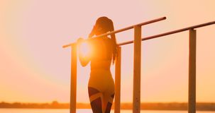 Woman resting while standing in the sunset bar near the rear view. A beautiful brunette woman with long hair stands near stock video footage