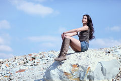 Woman resting on stone boulder. Young model sitting on big stone boulder looking away Stock Photos