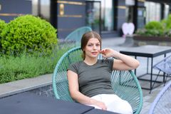 Woman resting at street cafe and sitting near green plant. Woman resting at street cafe and sitting in chair near green plant. Concept of beauty and leisure Royalty Free Stock Photos