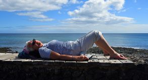 Woman resting in the sun on wall with the ocean in the background Stock Photo