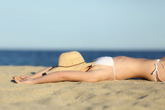 Woman resting sunbathing on the sand of the beach with a picture hat Stock Photography