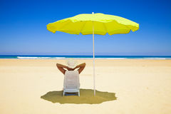 Woman resting under a beach umbrella Royalty Free Stock Images