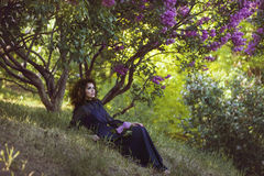 Woman is resting under a lilac bush in the park. Royalty Free Stock Images