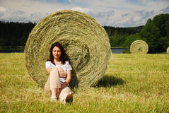 Woman resting under a straw bale Royalty Free Stock Images