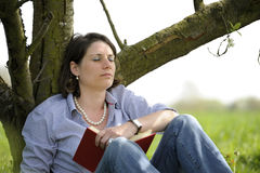 Woman resting under a tree Stock Photos