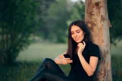 Woman Resting Under a Tree Checking Her Smartphone Royalty Free Stock Photography