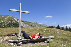 Woman resting under wooden cross. On the mountain, beautiful sunny summer day in the Alps Royalty Free Stock Images