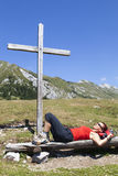 Woman resting under wooden cross. On the mountain, beautiful sunny summer day in the Alps Stock Photos