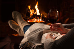 Woman resting with wine glass near fireplace Stock Images