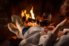 Woman resting with wine glass near fireplace Royalty Free Stock Photography