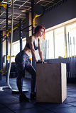 Woman resting after workout session in gym. Side view of female taking a break from endurance workout in gym Royalty Free Stock Image