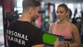 Woman restoring water balance and discussing workout with trainer in gym. Stock footage stock video footage