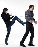 Woman restraining a man chained Stock Images