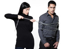 Woman restraining a man chained Stock Photography