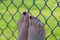 Woman rests feet on fence Stock Photo