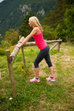 Woman rests at fence after workout in nature.  Royalty Free Stock Photo