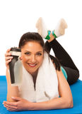 Woman rests after fitness workout with towel around her neck dri Royalty Free Stock Photo