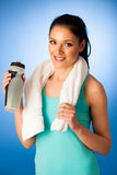 Woman rests after fitness workout with towel around her neck dri Stock Photo