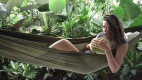 Woman rests on a hammock with coconut. In tropical garden stock video footage