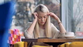 A blonde girl gets sad after looking at her smartphone. A woman rests her smartphone on a cafe table and touches her temples stock footage