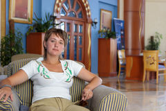 Woman rests in hotel. The woman sits on a armchair in a hotel Stock Image