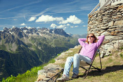 The woman rests in mountains. The woman rests on a summer slope in Alps Royalty Free Stock Photos