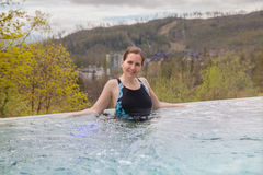 The woman rests in outdoor pool. In spring day, Tatranska Lomnica, Slovakia Stock Photo