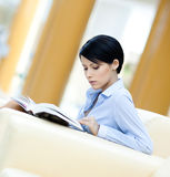 Woman rests at the sofa with book Stock Image