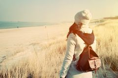 Woman with retro backpack on the beach looking at the sea Stock Image