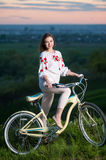 Woman with retro bike on the hill in the evening stock image