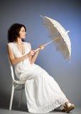 Woman in retro bridal dress with umbrella. Young woman in retro bridal dress with umbrella on background Royalty Free Stock Photos