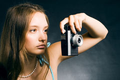 Woman with a retro camera. Young beautiful woman taking a photo with a retro camera Royalty Free Stock Photos