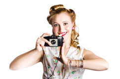 Woman with retro camera. Attractive smiling blond woman taking a picture with a black retro film camera on white background Royalty Free Stock Photo