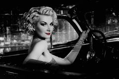 Woman  in retro car against. Woman with red lips in retro car against night city Stock Image